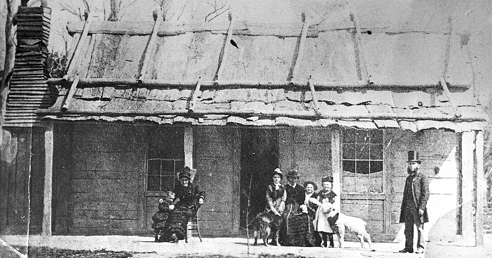 Ellen Kelly's release from prison in February 1881 is commemorated by this photo taken at the Kelly homestead. It shows from left, Alice King, Kate Kelly, Grace Kelly (with Faith, the Kelly cattle dog), Mrs Kelly, Jack King, Ellen King (feeding a pet lamb from a bottle) and the Rev. William Gould who had married Ellen Kelly and George King seven years earlier. Scarcely more than two months later, Constable Robert Graham visited here with Father Thomas Egan of Wangaratta and gained Mrs Kelly's help in defusing the ongoing Kelly rebellion. Image: Max Brown
